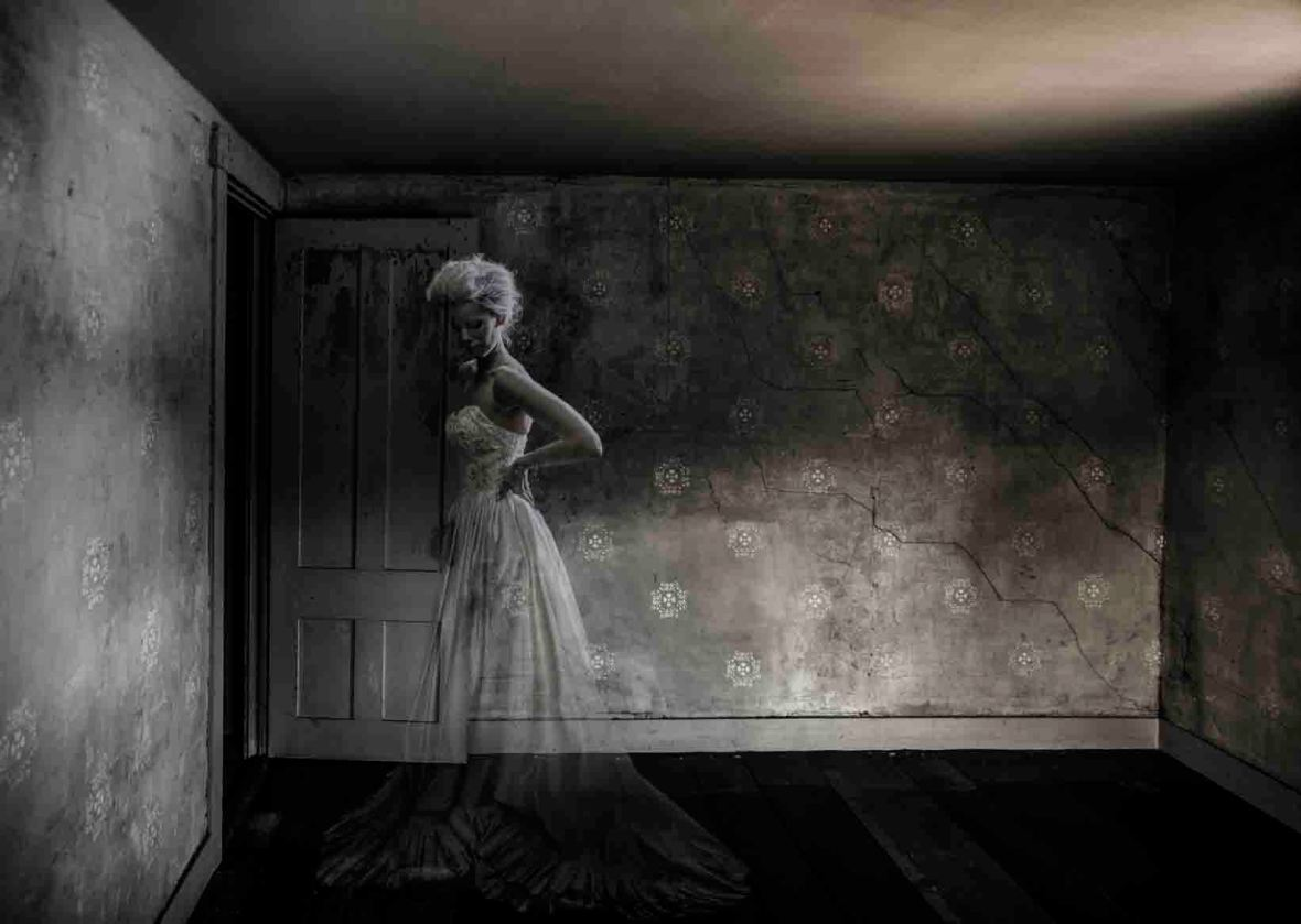 A ghost of a woman in a bridal dress in a run-down empty room